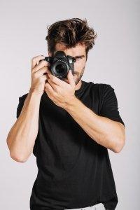 Homme qui tiens un appareil photo à son oeil et qui prends des appareils photos