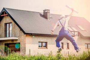 Homme sautant de joie devant une maison habité en salopette avec des papiers à la mains