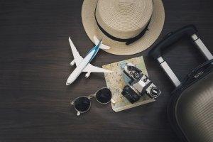 Image d'une carte, d'un appareil photo, d'une valise, d'un chapeau, de lunettes de soleil et d'un avion miniature joliment disposé sur une table de couleur foncée