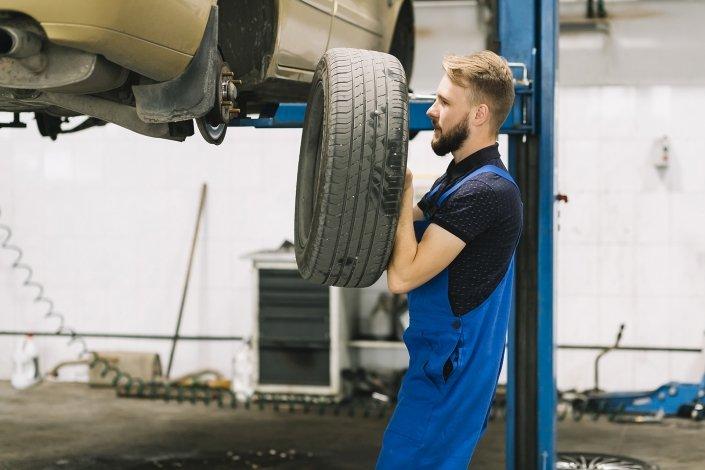 Garagiste qui change les roue d'une voiture qui est surélevée