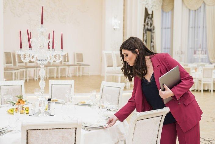 Femme qui remets en place des assiettes disposée joliment sur une table de réception