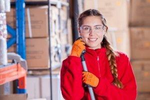 Femme qui se trouve dans un hangar avec une polaire rouge et un balais dans la mains